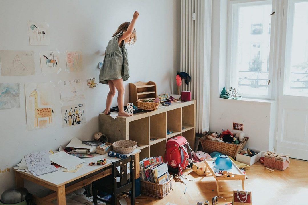 Kind klettert aud Schrank in ihr ungeordnetes Kinderzimmer bei Foto Shooting zuhause in Friedrichshain